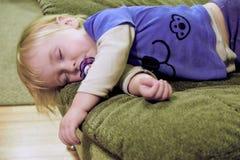 Behandla som ett barn sover på soffan Arkivbild