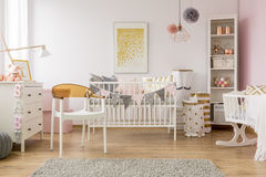 Behandla som ett barn sovrummet med vit stol royaltyfria foton