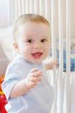 Behandla som ett barn ställningar vid vit säng Royaltyfri Fotografi