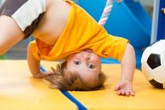 Behandla som ett barn ställningar som är uppochnervända på den matta idrottshallen Arkivfoton