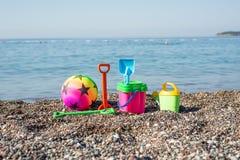 Behandla som ett barn strandutrustning, leksaker på ett Pebble Beach Arkivfoto