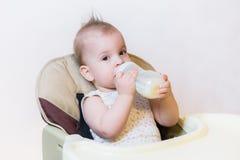 Behandla som ett barn suger mjölkar från en flaska hemma Arkivfoto