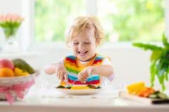 Behandla som ett barn ?ta gr?nsaker Fast mat f?r sp?dbarn arkivfoton