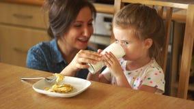 Behandla som ett barn tagandefrukosten med kefir Hon har en vit mustasch på hennes kant Mamma- och dotterskratt i köket arkivfilmer