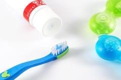 Behandla som ett barn tandborsten och tandkräm på vit bakgrund Fotografering för Bildbyråer