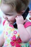 behandla som ett barn telefonen för cellflickaholdingen Royaltyfria Bilder