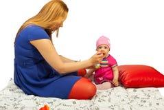 behandla som ett barn äter att ge moderpuré till Arkivbild