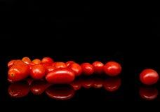 Behandla som ett barn tomater, körsbärsröda tomater och vattendroppe på svart bakgrund med reflexion Royaltyfria Foton