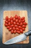 Behandla som ett barn tomater på skärbräda med kniven Royaltyfri Fotografi