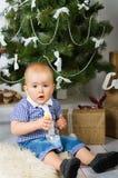 Behandla som ett barn under julgranen Arkivfoton