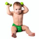Behandla som ett barn ungen, litet barn i gröna blöjor som gör övningar med dumbbel Royaltyfri Bild