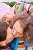behandla som ett barn utomhus- föräldrar för kyssen Royaltyfria Foton