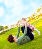 behandla som ett barn utomhus- leka för flickamoder Arkivfoto