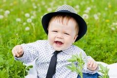 behandla som ett barn utomhus- övre för pojkepåkläddgräs Arkivbilder