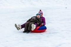 Behandla som ett barn vintern som sledding på den Ural floden Arkivbild