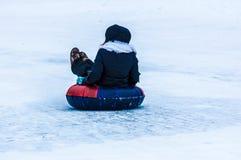 Behandla som ett barn vintern som sledding på den Ural floden Arkivfoto