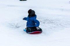 Behandla som ett barn vintern som sledding på den Ural floden, Arkivbild