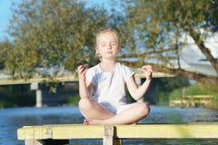 Behandla som ett barn yoga Lotus poserar en övande yoga för barn utomhus arkivbilder