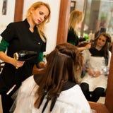 Behandling för frisördanandehår till en kund i salong Royaltyfri Bild