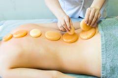 Behandlung der Rückseite und des Dorns mit gelber Jade Das Mädchen auf der Massagetabelle behandelt zurück Masseur, der Massage t lizenzfreie stockfotografie