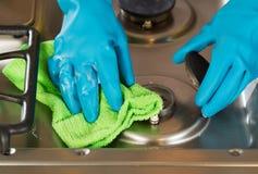 Behandschuhte Hände, die Seife von der Herdplattestrecke mit microfiber entfernen Lizenzfreie Stockbilder