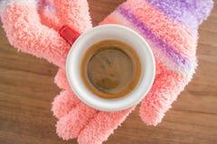 Behandschuhte Hände, die Tasse Kaffee halten Stockfotos