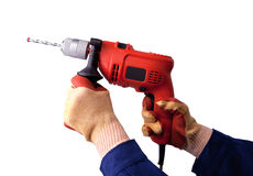 Behandschuhte Hände mit elektrischer Bohrmaschine Stockfotos