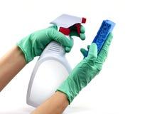 Behandschuhte Hände mit Schwamm und Reinigungsspray stockfotografie