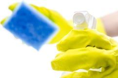 Behandschuhte Hand, die einen reinigenden Spray und einen Schwamm anhält Stockbilder