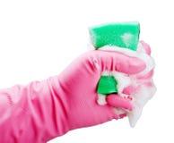 Behandschuhte Hand drückt einen Schwamm für Reinigung zusammen stockbild