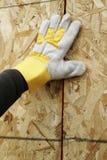 Behandschuhte Hand-und Furnierholz-Wand Lizenzfreies Stockfoto