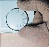 Behandskad hand som förändrar uppvärmningtermostaten. Royaltyfri Fotografi