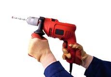 Behandskade händer med den elektriska drillborren Arkivfoton