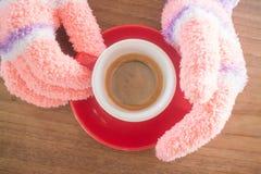Behandskade händer som rymmer koppen kaffe Arkivfoto