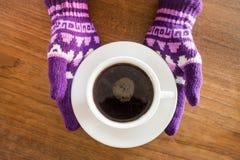 Behandskade händer som rymmer koppen kaffe Royaltyfri Fotografi