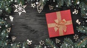 Behang van de wintervakantie op zwarte achtergrond Rode gift en houten speelgoed Sparren rond Hoogste mening De groetkaart van Ke royalty-vrije stock afbeelding