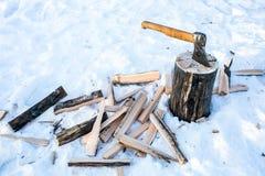Behauen Sie im Block und im Brennholz auf Schneehintergrund Stockfoto