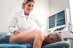 Behaupteter blond-haariger Massagetherapeut, der ihre Arbeit liebt stockfotos
