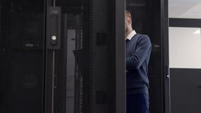Beheerder die in serverruimte lopen en bij laptop typen stock video