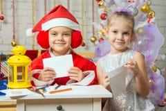 Behelfsmäßige Santa Claus und Fee bereiten Glückwunschbriefe vor Stockfotografie
