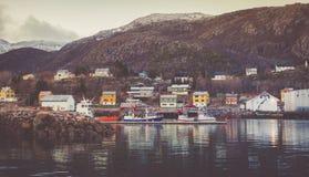 Beherbergten Sie mit festgemachten Booten und Yachten mit Schnee-mit einer Kappe bedeckten Spitzen im Hintergrund im Fischerdorf stockbilder