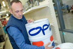 Behilfliche bewegliche Farbe des Verkäufers im Heimwerkenspeicher stockfotografie
