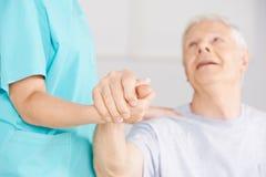 Behilfliche haltene Hand der Krankenpflege des älteren Mannes Stockbild