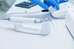 Behilfliche ` s Hände konfiguriert zahnmedizinische Ausrüstung in Zahnarzt ` s Büro Schließen Sie oben, selektiver Fokus zahnheil Stockfoto