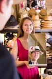 Behilflicher haltener Spiegel und Mann seine Reflexion in den Hüten zeigen Stockfoto