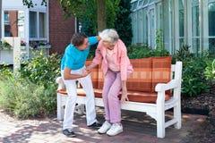 Behilfliches Neigen der Sorgfalt zu einer älteren Dame Stockbild