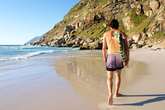 Behind of attractive surfer walking in sand by water Royalty Free Stock Photo