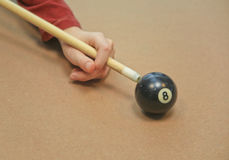 Behind the 8 Ball. A young man having fun with an 8 ball while playing pool.. He is pretending to behind the eight ball on a tan covered table Royalty Free Stock Photos
