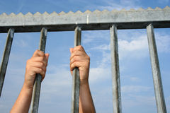 Behind bars. Hands holding on to bars Royalty Free Stock Photos