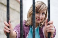 Behind the bars. Cute girl is looking through the bars royalty free stock image
